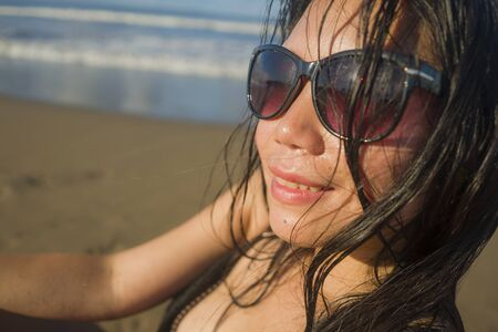 natural lifestyle portrait of young sexy and cool Asian Japanese woman in swimsuit and sunglasses on beautiful beach paradise feeling relaxed and happy enjoying holidays carefree 版權商用圖片