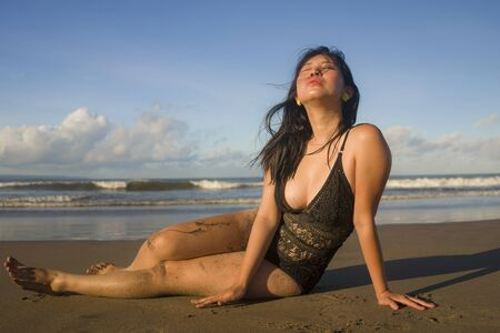 natural lifestyle portrait of young attractive and happy Asian Japanese woman in swimsuit playful on sand at beautiful beach paradise feeling relaxed and cheerful enjoying holidays carefree