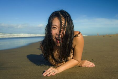 natural lifestyle portrait of young attractive and happy Asian Korean woman in swimsuit playful on sand at beautiful beach paradise feeling relaxed and cheerful enjoying holidays carefree