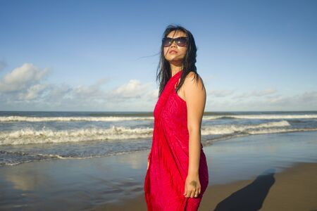 outdoors Summer lifestyle portrait of young sexy and relaxed Asian Korean woman wearing sarong and cool sunglasses at the beach walking by the sea enjoying holiday travel destination