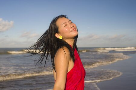 young attractive and happy Asian Korean woman in sarong walking by the sea relaxed and cool feeling free enjoying holiday at beautiful beach in Summer vacation and travel destination concept
