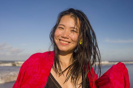 outdoors lifestyle portrait of young beautiful and happy Asian Korean woman in swimsuit at the beach playing carefree with sarong enjoying Summer holiday feeling free and blissful