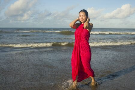 young sweet and happy Asian Korean woman in sarong at beautiful beach walking by the sea relaxed and blissful enjoying Summer holiday travel feeling free in Asia travel destination concept