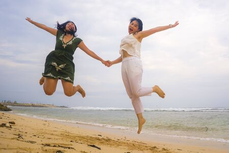 young beautiful and happy couple of attractive Asian Korean women jumping on the air together at the beach enjoying holidays having crazy fun feeling free and joyful in girls friendship concept