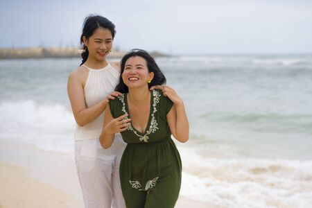 young beautiful and happy couple of attractive Asian Korean women walking together relaxed at the beach enjoying holidays in love or close girlfriends relationship concept