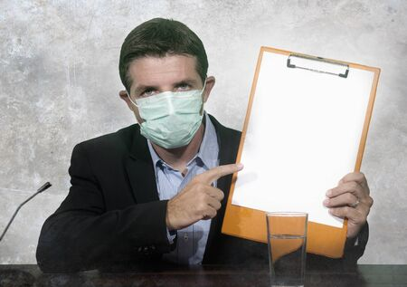 health organization executive man in medical face mask giving information at press conference about virus outbreak showing clipboard with blank copy space warning about pandemic 版權商用圖片 - 140959042