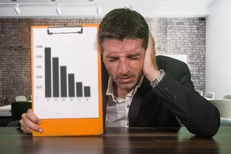 depressed and worried businessman holding clipboard showing graph reporting company financial crisis and problems feeling concerned and frustrated in corporate work difficulties concept