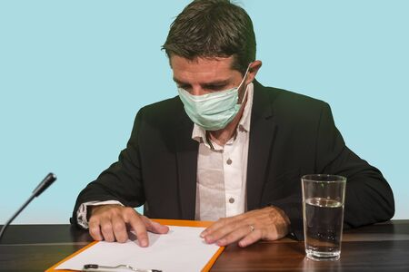 health organization executive man in medical face mask giving information at press conference about virus outbreak showing clipboard with epidemic disease spread warning about pandemic