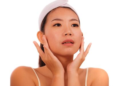 isolated portrait young beautiful and happy Asian Korean woman applying skincare wrinkle prevention treatment or aging beauty product on her face in makeup cosmetic and healthy lifestyle Standard-Bild