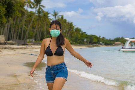 use of medical face mask in public places- young attractive Asian Korean woman enjoying beach holidays wearing bikini and protective facial mask in prevention vs virus infection