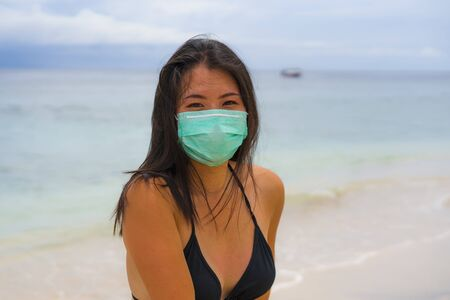 use of medical face mask in public places- young attractive Asian Chinese woman enjoying beach holidays wearing bikini and protective facial mask in prevention vs virus infection