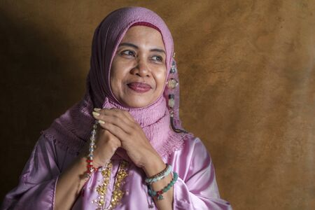 isolated studio portrait of happy and positive senior muslim woman in her 50s wearing traditional Islam hijab head scarf praying holding prayer beads in Islamic culture and religion concept