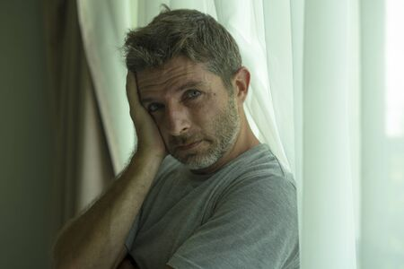 dramatic indoors portrait of mid adult man crying sad and depressed standing at bedroom window in despair at home feeling worried and overwhelmed suffering depression and anxiety problem