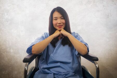 isolated portrait of young beautiful and happy Asian Korean woman in hospital patient gown sitting on wheelchair smiling positive recovering from accident or virus infection