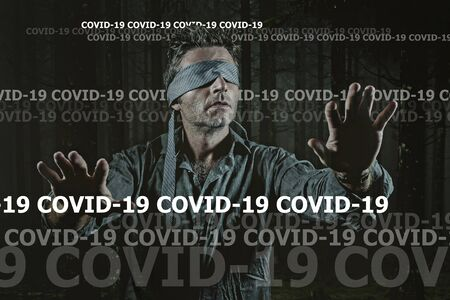 covid-19 virus outbreak conceptual image on young scared and blindfolded man lost in the dark and confused on the load of fake news and information about coronavirus pandemic 版權商用圖片