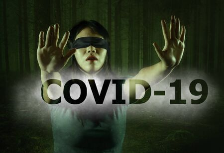 covid-19 virus outbreak conceptual image on young scared and blindfolded Asian woman lost in the dark and confused on the load of fake news and information about coronavirus pandemic