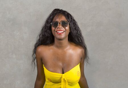 young stylish and happy black African American woman  in yellow dress and sunglasses posing confident and playful isolated on dark background looking at camera in cool attitude 写真素材 - 143254302