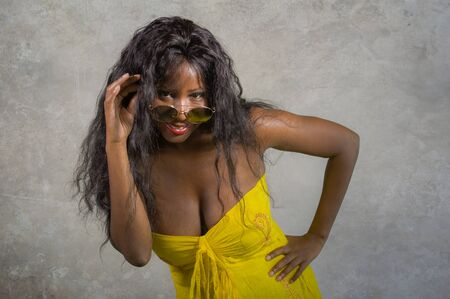 young stylish and happy black African American woman  in yellow dress and sunglasses posing confident and playful isolated on dark background looking at camera in cool attitude