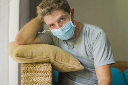 covid-19 virus lockdown - sad and worried man on his 30s or 40s covered with medical mask thinking and feeling scared in quarantine following stay at home instructions to contain virus pandemic