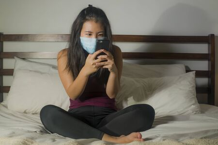 covid-19 quarantine home lockdown - young beautiful scared and overwhelmed Asian woman in protective mask checking online news worried about coronavirus pandemic Foto de archivo