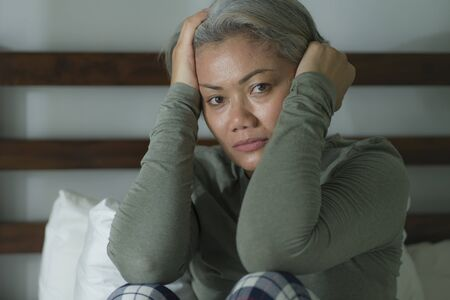 mature lady crisis - attractive middle aged woman with grey hair sad and depressed in bed feeling scared and lonely thinking worried about covid-19 virus pandemic during home lockdown