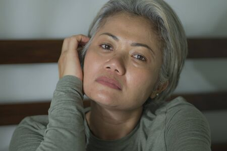 mature lady crisis - indoors lifestyle portrait of middle aged woman with grey hair sad and depressed in bed feeling frustrated and lonely thinking about aging lonely suffering depression