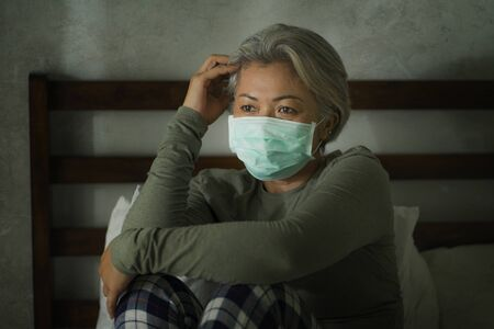 dramatic portrait of scared and worried middle aged woman 50s with grey hair and protective mask during covid-19 virus crisis home lockdown quarantine thoughtful in fear and stress