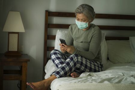 attractive and worried middle aged woman 50s with grey hair and protective mask checking online news with mobile phone during covid-19 virus home lockdown quarantine scared and sad Фото со стока