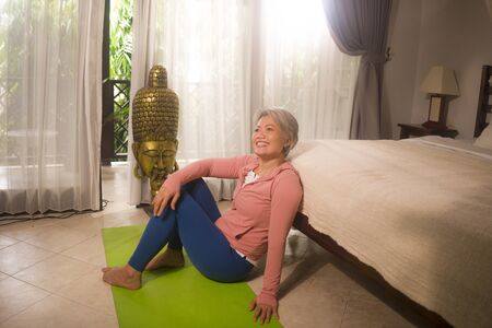 home lifestyle - beautiful and happy mature woman with gray hair on her 50s smiling after fitness and yoga exercise at Asian deco bedroom in wellness and healthy aging concept