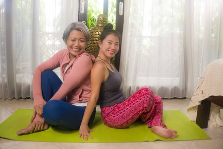 happy girlfriends enjoying yoga and fitness workout at home - two beautiful Asian women posing together after exercise session smiling and laughing in female friendship and healthy lifestyle 版權商用圖片