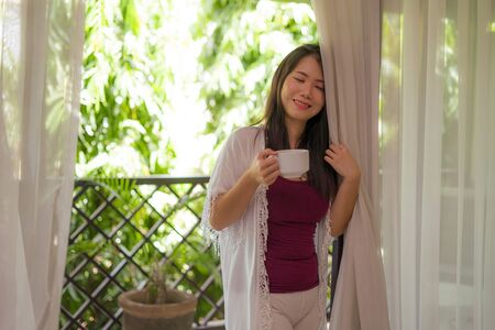 lifestyle portrait of young happy and beautiful Asian Chinese woman having morning coffee or tea at hotel terrace or home balcony smiling relaxed and cheerful in travel destination concept