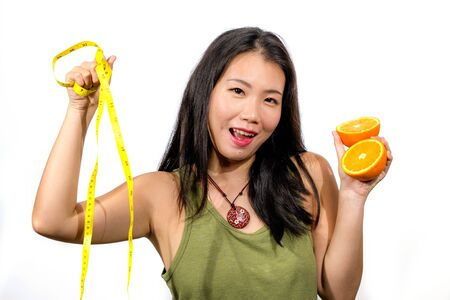 young happy and beautiful Asian Korean woman holding orange fruit and tape measure smiling cheerful in diet and weight loss through healthy natural nutrition isolated on white 写真素材 - 145104147