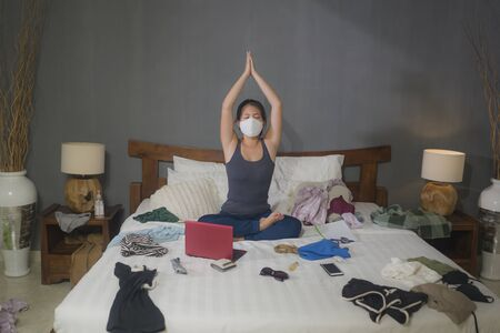 relaxation and yoga in times of coronavirus - young beautiful and happy Asian Korean woman doing yoga meditation exercise on chaotic and messy bed during covid-19 home lockdown quarantine 版權商用圖片 - 145693747