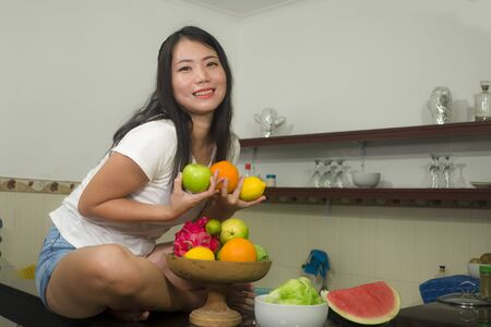 vegetable food and diet - home lifestyle portrait of young beautiful and happy Asian Chinese woman at domestic kitchen smiling cheerful in healthy nutrition and dieting concept