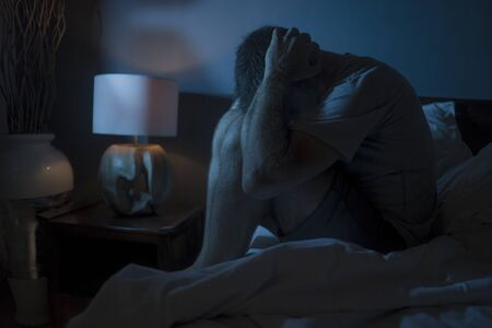 dramatic portrait in the dark of attractive depressed and worried man on bed suffering depression crisis and anxiety feeling lost sitting sleepless in insomnia and life problem concept Stock Photo