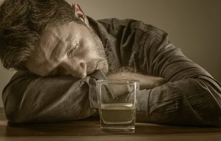 young messy and drunk alcohol addict man drinking whiskey glass at home sitting thoughtful and depressed as alcoholic suffering alcoholism problem and addiction intoxicated and lost Banco de Imagens
