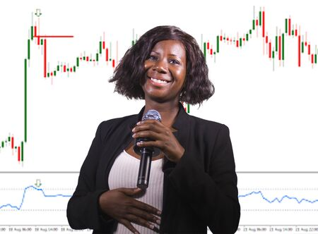 successful stocks and forex market trading - young beautiful and happy afro American business woman and trader coaching investment strategies and financial success on candlesticks graph Imagens