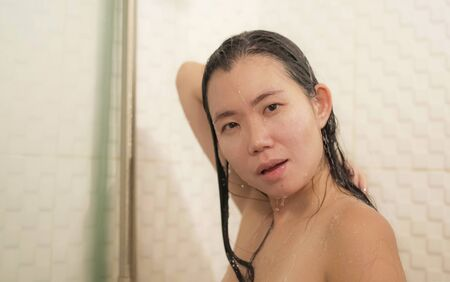 home lifestyle portrait of young beautiful and happy Asian Chinese woman taking a shower in the bathroom washing her hair enjoying morning hygiene in skincare and beauty concept
