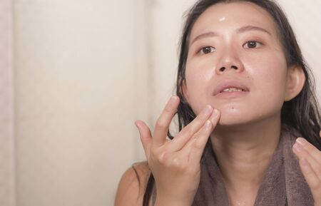 young happy and beautiful Asian Korean woman applying moisturizer facial cream and beauty treatment at home bathroom in morning routine smiling cheerful and fresh
