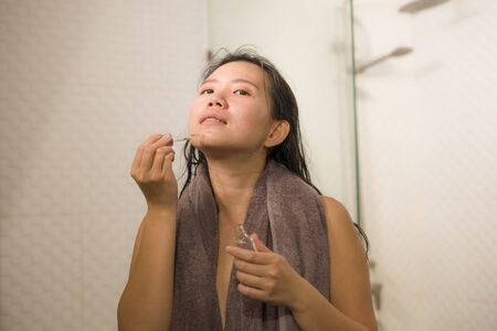 home lifestyle portrait of young beautiful and happy Asian Chinese woman applying serum facial skin care and face treatment in the bathroom enjoying morning routine in beauty concept