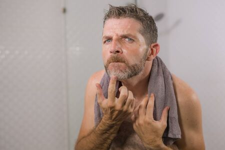lifestyle portrait of mid adult attractive concerned and upset man at home bathroom looking at the mirror grey hair on his beard worried about aging 免版税图像