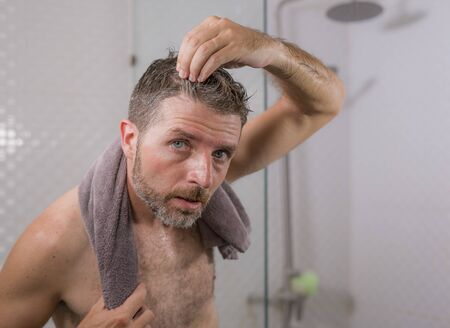 lifestyle portrait of mid adult attractive concerned and upset man at home bathroom searching and finding gray hair looking at the mirror worried about aging