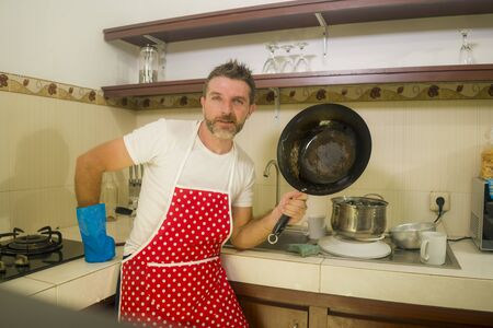 happy and attractive man in red apron smiling at kitchen washing dishes and cooking pan cheerful doing housework and domestic chores enjoying home lifestyle