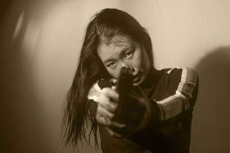edgy cinematic portrait of young attractive and dangerous special agent woman or Asian mobster girl holding handgun pointing the gun fierce in Hollywood movie style