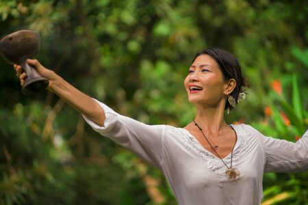 mind and body connection - beautiful and happy healer Asian woman holding incense cup doing ritual traditional healing dance at green tropical forest in wellness and healthy lifestyle