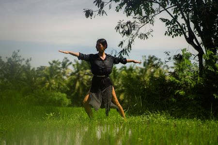 outdoors yoga and meditation at rice field - attractive and happy middle aged Asian Japanese woman enjoying yoga and relaxation in connection with the nature in healthy lifestyle and wellness Archivio Fotografico