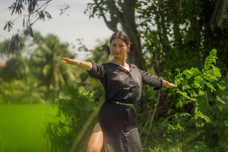 outdoors yoga and meditation at rice field - attractive and happy middle aged Asian Korean woman enjoying yoga and relaxation in connection with the nature in healthy lifestyle and wellness Archivio Fotografico