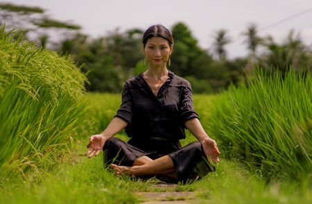 outdoors yoga and meditation at rice field - attractive and happy middle aged Asian Chinese woman enjoying yoga and relaxation in connection with the nature in healthy lifestyle and wellness
