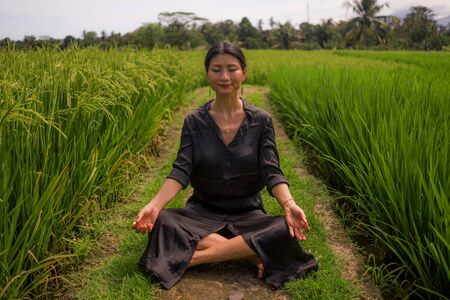 outdoors yoga and meditation at rice field - attractive and happy middle aged Asian Korean woman enjoying yoga and relaxation in connection with the nature in healthy lifestyle and wellness Фото со стока