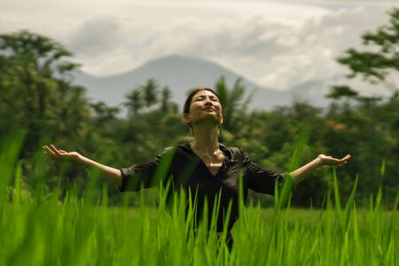 outdoors yoga and meditation at rice field - attractive and happy middle aged Asian Japanese woman enjoying yoga and relaxation in connection with the nature in healthy lifestyle and wellness